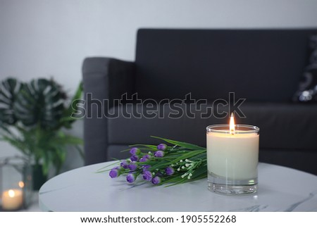 luxury aroma lighting aromatic scented candle glass displayed on the white marble table with bouquet of flowers to creat romantic and relax ambient with background of grey sofa in living room Royalty-Free Stock Photo #1905552268