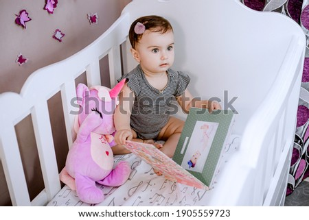 Amazed, cute baby opening her photo album in crib and looking at her mom carefully
