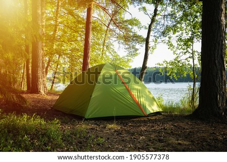Hiking travel life style passion concept picture of tent camp side place in forest. Forest camp with lake view.