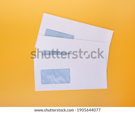Blank envelopes with address window on yellow background. White paper envelopes mockup for business correspondence, postal stationery and corporate lettering Royalty-Free Stock Photo #1905644077