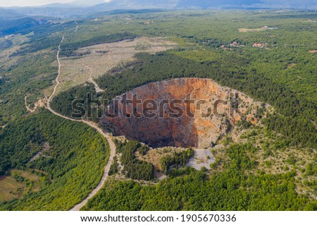 Red Lake (Croatian: Crveno jezero) is a collapse doline (collapse sinkhole) containing a karst lake close to Imotski, Croatia. It is 530 metres deep, thus it is the largest collapse doline in Europe.  Royalty-Free Stock Photo #1905670336