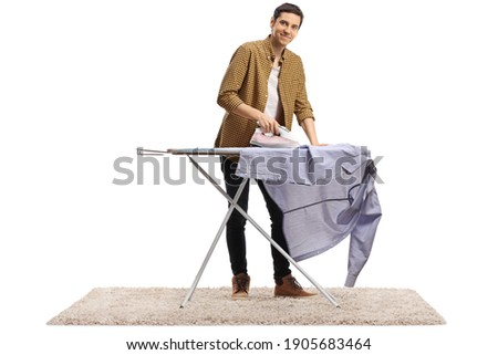 Full length portrait of a young man ironing a shirt and smiling at camera isolated on white background