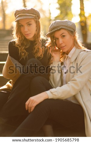 Young sisters sitting on stairs in fashion clothes. Fall picture