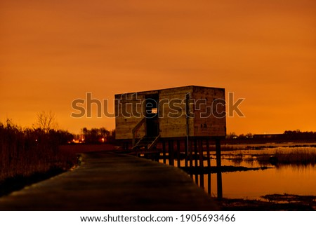 Observation cabin in the dark along The Vinne in Belgium. The light pollution turns the picture completely orange. Wooden path is leading you to the wooden cabin, perfect spot for bird watching.
