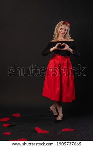 Girl standing around cardboard hearts symbol, flirting board, on the floor hearts lovely romance. holiday. event forever, frame in red dress girl, barefoot