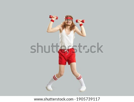 Full body funny tired weak thin skinny man in glasses, retro gym headband, white tank top and red shorts holding heavy fitness dumbbells and doing sports workout exercise isolated on gray background
