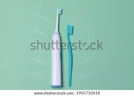 Two toothbrushes, an electric ultrasonic and an ordinary mechanical one on a light green background, top view. Oral hygiene, daily care.
