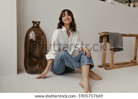 Joyful brunette curly woman in trendy pants and white shirt smiles and looks into camera. Pretty lady in jeans sits on floor in bathroom. Royalty-Free Stock Photo #1905757669