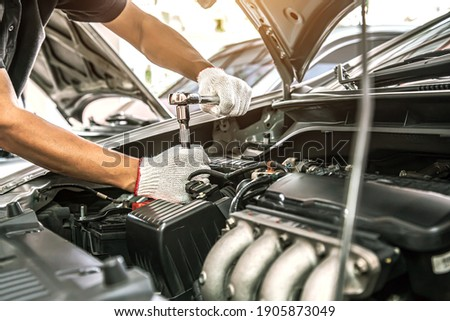 Close-up hands of auto mechanic are using the wrench to repair and maintenance auto engine is problems at car repair shop. Concepts of car care check and fixed and services insurance. Royalty-Free Stock Photo #1905873049