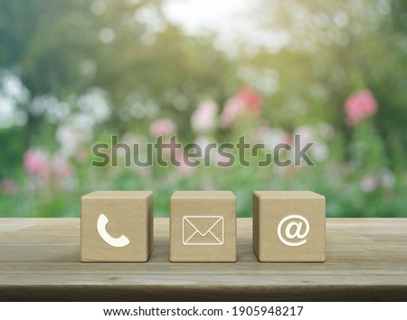 Telephone, mail, email address on wood block cubes on wooden table over blur pink flower and tree in garden, Business customer service and support concept