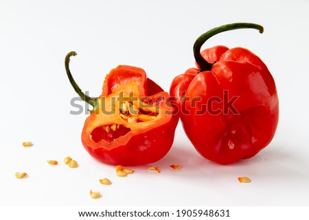 Isolated image of a whole and half of a habanero red chilli pepper with seeds around on a white background. Royalty-Free Stock Photo #1905948631