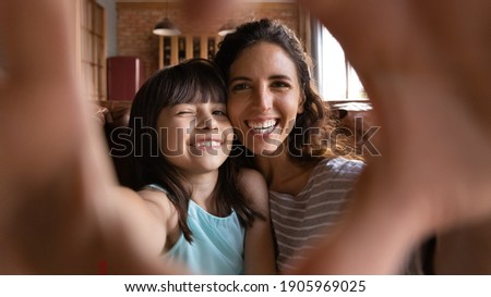 Head shot portrait happy mother and daughter taking selfie, showing heart gesture, looking at camera through fingers, sitting on couch at home, smiling mum with little girl having fun together