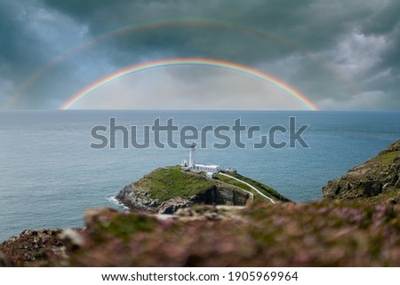 Colourful double rainbows in seascape over the ocean horizon with storm clouds dramatic sky and white lighthouse on top of island peninsular coastline in beautiful calm blue ocean sea south stack Royalty-Free Stock Photo #1905969964