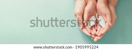 Adult and child hands holding lung, world tuberculosis day, world no tobacco day, corona covid-19 virus, eco air pollution; organ donation concept Royalty-Free Stock Photo #1905995224