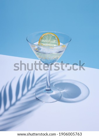 Summer stationery still life scene made with glass, dried lemon, drink, and trend palm shadow on blue pastel background. Summer vacation refreshment concept. Long shadow and refraction pattern. Royalty-Free Stock Photo #1906005763