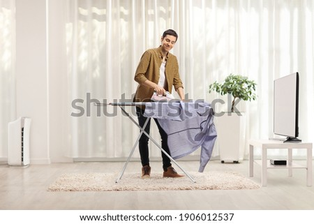 Cheerful young man ironing a shirt at home in a living room