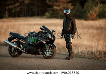 Motorcycle driver in a helmet and leather jacket stands on the road next to a sports motorcycle Royalty-Free Stock Photo #1906015840