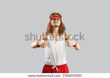 Funny nerdy guy giving you motivation to exercise. Skinny man in gym headband and tank top standing isolated on grey background and showing thumbs up gesture. Sports workout and fitness humour concept