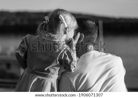 A little girl with two ponytails and a dress whispers a secret in her father's ear. Daughter and parent. Black and white photo.