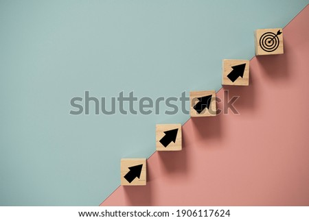 Virtual target board and arrow which print screen to wooden cube block on blue and pink background. Business achievement goal and objective target concept.