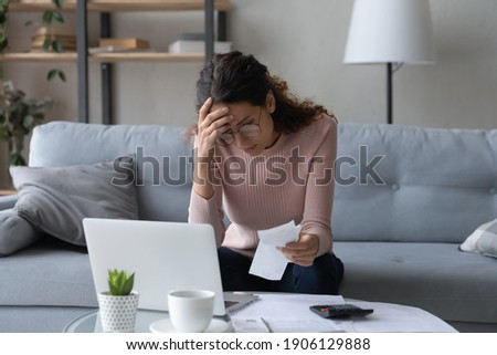 Unhappy young woman in glasses feeling stressed calculating monthly expenses at home, facing financial problems or lack of money for utility household or rental payments, bankruptcy concept. Royalty-Free Stock Photo #1906129888