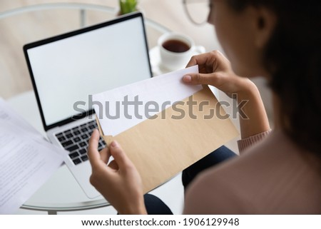 Close up young woman opening envelope with letter, feeling curious of getting news. Back rear view millennial lady receive postal mail with important document, invitation or bank notification. Royalty-Free Stock Photo #1906129948