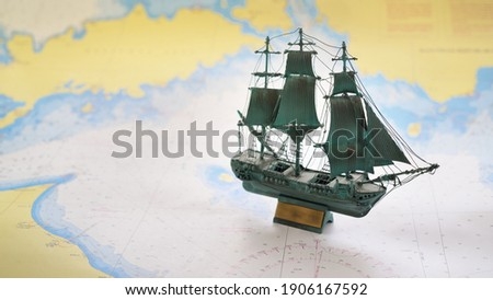 Vintage scale model of the historical tall ship and old white nautical chart close-up. Planning travel, sailing accessories, concept art, graphic resources, objects, collecting Royalty-Free Stock Photo #1906167592