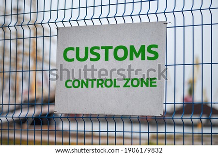 Customs control zone sign with green letters on metal fence, warning about entering special area. Security checkpoint of logistics complex, vehicle inspection point. Border symbol.