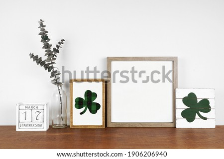 Mock up wood frame with St Patricks Day decor on a wood shelf. Shabby chic wood signs, calendar and green branches. Square frame against a white wall. Copy space. Royalty-Free Stock Photo #1906206940