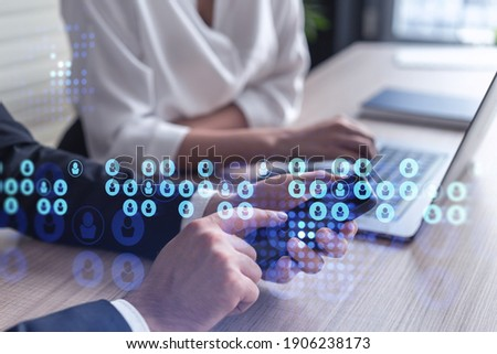 Two HR specialists in formal wear analyzing the market using phone to find new interns for recruitment program at international consulting company. Social networking and media hologram icons.