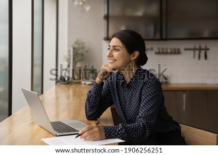 Inspired mixed race female sit by table with laptop at home kitchen look at window engaged by amazing idea. Dreamy young indian woman writer create new exciting story prepare to put it down on paper