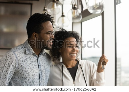 Happy afro american husband wife new studio apartment owners stand by panoramic window hold keys dreaming. Excited young black spouses becoming homeowners enjoy splendid city picture from modern flat