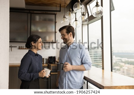 Happy mixed race family couple drink tea coffee at new modern apartment flat by picture window. Loving young spouses indian wife caucasian husband enjoy talking holding cups with hot drinks at kitchen