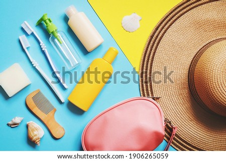 Luggage and summer travel accessories bag, toiletries kit. Flat lay composition object photography. Soap bar, toothbrushes, empty bottles for cosmetics, sunscreen cream, bag and hat Royalty-Free Stock Photo #1906265059