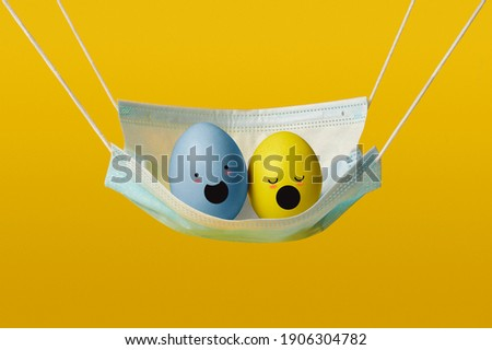happy easter eggs during a pandemic in a medical mask on yellow background. singing eggs
