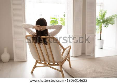 Back view of calm young woman sit rest in cozy modern chair in living room stretch breathe fresh air. Happy female renter relax in armchair at home look in window think or visualize enjoy weekend. Royalty-Free Stock Photo #1906314622
