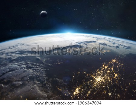 View on planet Earth from space. Cities lights and continents. Civilization on planet. Moon on background. Elements of this image furnished by NASA Royalty-Free Stock Photo #1906347094