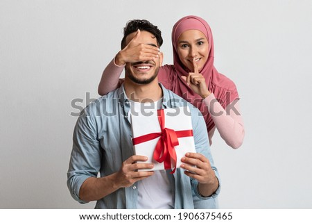 Surprise Gift. Romantic Muslim Woman Covering Her Husband's Eyes And Giving Present, Loving Islamic Lady Showing Shh Silence Gesture At Camera While Greeting Her Man With Valentine's Day Or Birthday