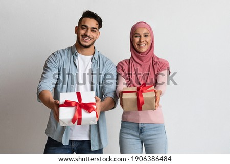Happy arab man and woman in hijab showing gift boxes at camera, cheerful muslim couple posing with presents over grey studio background, joyful islamic spouses greeting with holidays, free space