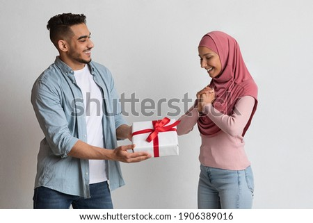 Loving arab man giving present to his excited muslim girlfriend in hijab, surprising islamic wife with gift box over grey studio background, greeting with Valentine's or International women's day