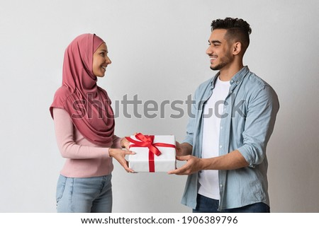 Happy muslim couple giving Valentine gifts to each other. Romantic arab man and islamic woman in hijab exchanging presents over grey studio background, celebrating holidays together, free space