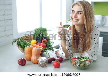 Woman on a diet. Young and happy woman eating healthy salad sitting on the table with green fresh ingredients indoors. High quality photo Royalty-Free Stock Photo #1906529038