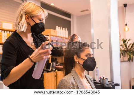 Hairdresser with face mask combing the client's hair with hairspray. Reopening with security measures of Hairdressers in the Covid-19 pandemic Royalty-Free Stock Photo #1906543045