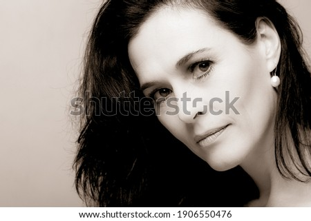 Portrait of a mature brunette woman sitting and contemplates the realities of life Royalty-Free Stock Photo #1906550476