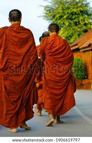 monks dressing orange robe during reception of alms, around buddhist temple Royalty-Free Stock Photo #1906619797