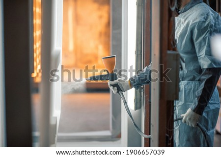 Painter in protective wear paints metal products with powder paint. Powder coating process at the manufacturing. High quality photo Royalty-Free Stock Photo #1906657039
