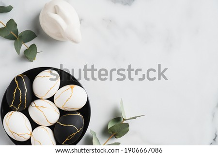 Elegant Easter flatlay composition. Luxury Easter eggs decorated with gold, rabbit bunny, eucalyptus leaves on marble table. Flat lay, top view Royalty-Free Stock Photo #1906667086