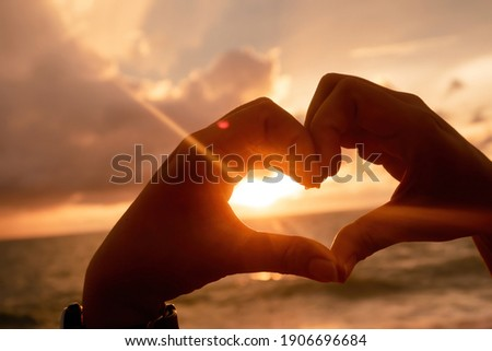 Concept of love The hand of the person making up the heart is raised for a picture with the sunset over the sea.