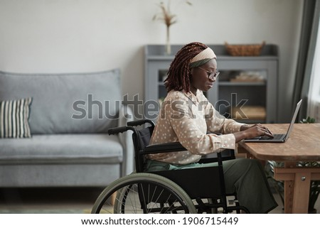 Side view portrait of young African-American woman using wheelchair while working from home in minimal grey interior, copy space Royalty-Free Stock Photo #1906715449