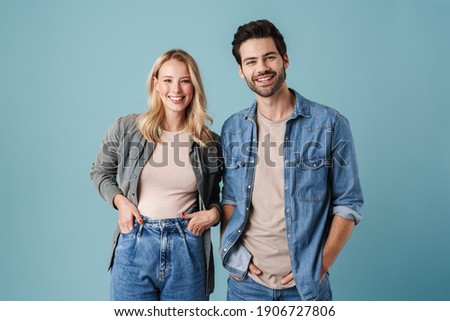 Young beautiful caucasian man and woman smiling and posing at camera isolated over blue background Royalty-Free Stock Photo #1906727806